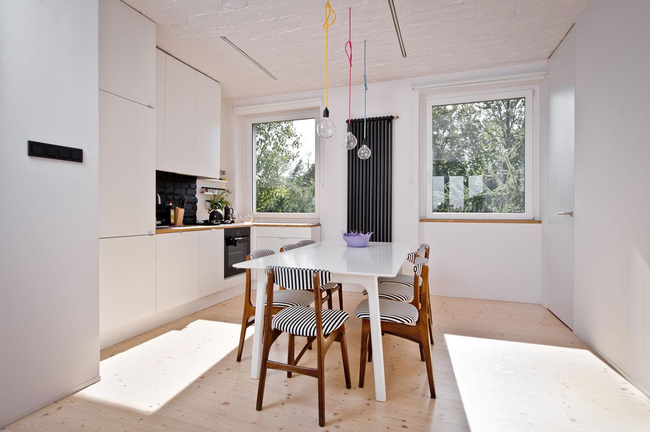 kuchnia z jadalnią z dużym białym stołem i odnowionymi krzesłami